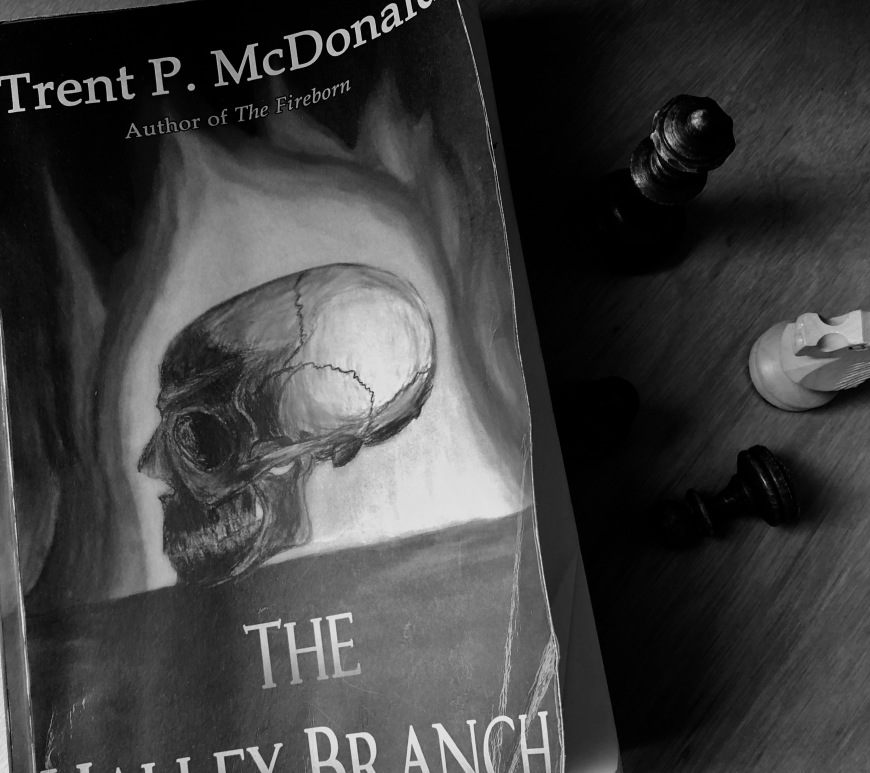 black and white picture of the book The Halley Branch by Trent P. McDonald on the right some chess pieces
