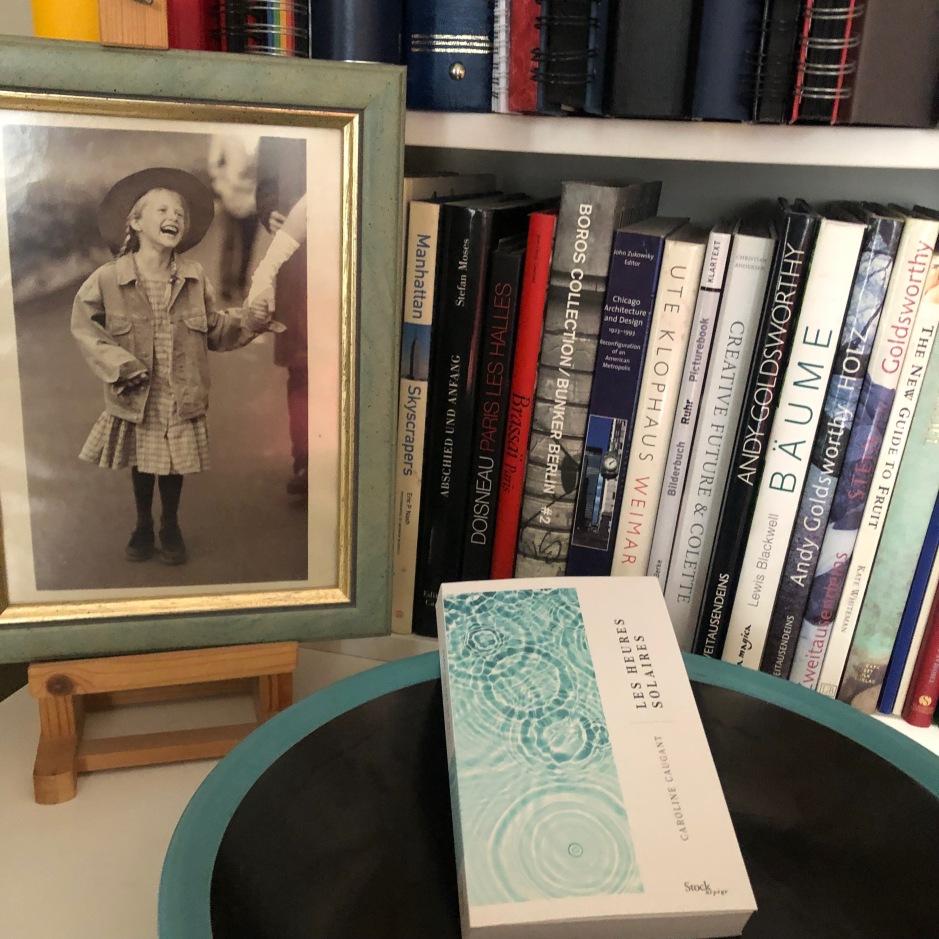le livre les heures solaires dans un bol devant des livres d'art à côté d'une photo d'une petite fille