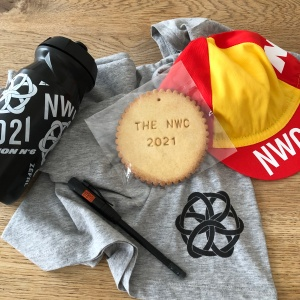 A black cycling bottle by Zefal with the NWC logo and name, finisher medal biscuit with THE NWC 2021, red and yellow solar cap, black pencil with orange logo by Faber Castel.